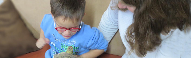 ילד מחזיק צב בביקור בפינת חי בנופש חנוכה