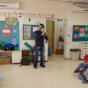 גיא מנגן לילדים בפעילות הסברה בנעלה